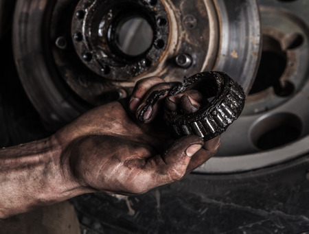 Dirty man hand with gear and car wheel Stock Photo