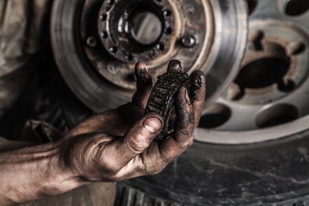 manos limpias: Sucia mano del hombre con el engranaje y la rueda de coche
