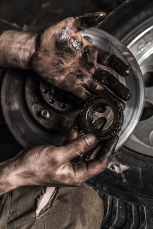 dirty car: Dirty man hand with gear and car wheel Stock Photo