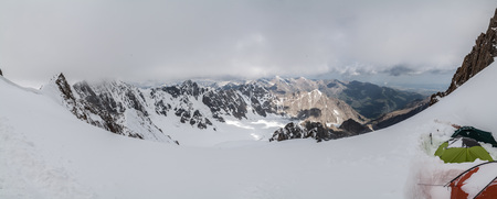 Cloudy pano view from high mountain with tents at Tian Shan mountains, Kyrgyzstan Stock Photo