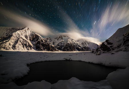 Amazing night landsape with snow peaks, star trails and small lake foreground Stock Photo