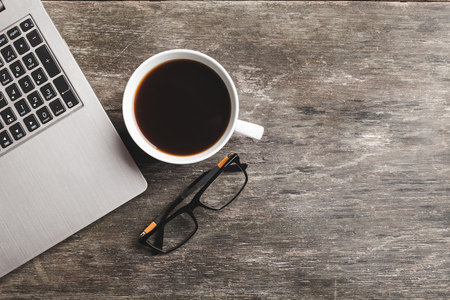 Top view of notebook, glasses and coffee. Business still life on old wooden table