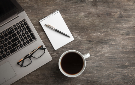 Top view of notebook, notepad, glasses and coffee. Business still life on old wooden table Reklamní fotografie
