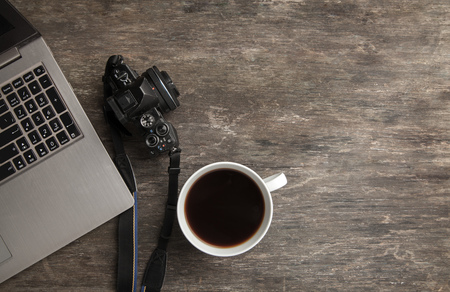 Top view of notebook, camera and coffee. Business still life on old wooden table