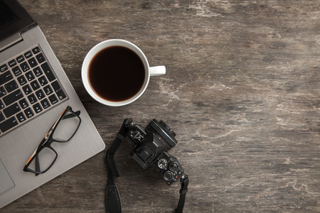 Top view of notebook, camera, glasses and coffee. Business still life on old wooden table