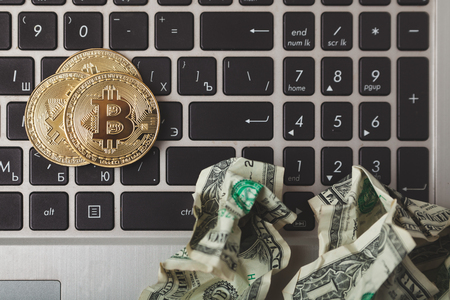 Crypto currency. Gold bitcoin coins and crumpled dollars on laptop keyboard