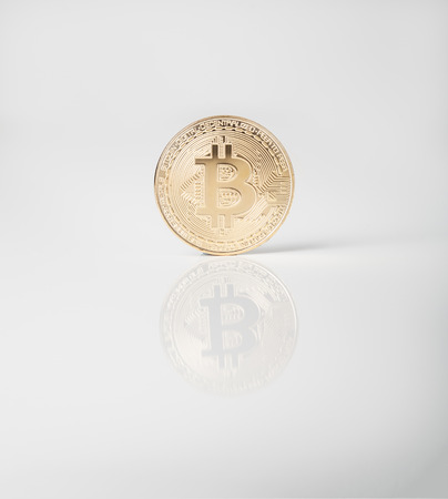 Crypto currency. Bitcoin gold coin on white background with reflection
