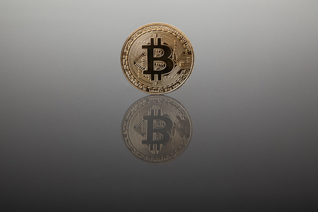 Crypto currency. Gold bitcoin on gray glass with reflection Reklamní fotografie