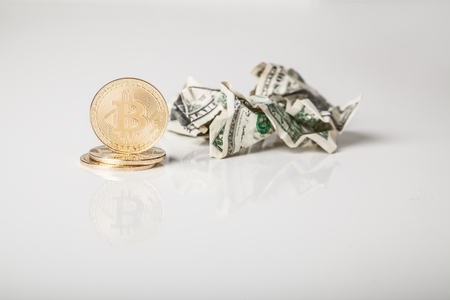 Crypto currency. Gold bitcoin coins and crumpled dollars on white background Reklamní fotografie