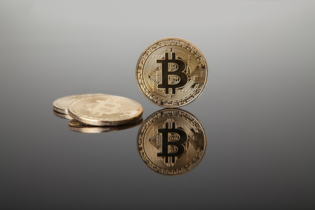 Crypto currency. Gold bitcoins on gray glass with reflection Reklamní fotografie