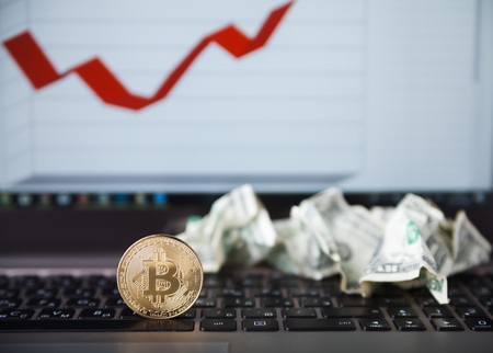 Crypto currency. Gold bitcoin coins and crumpled dollars on laptop keyboard with graph in background