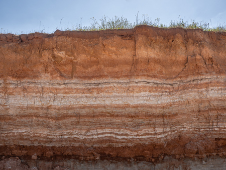 Natural cut of soil with different layaers, grass and blue sky Banco de Imagens