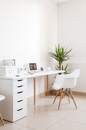 Modern hipster workplace. Small white office with table, chair, notebook and cup