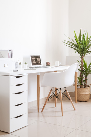 Modern hipster workplace. Small white office with table, chair, notebook, cup and plant