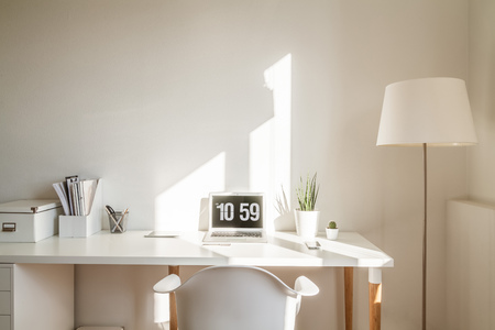 Modern hipster workplace. Small white office with table, chair, notebook, plant and floor lamp Reklamní fotografie