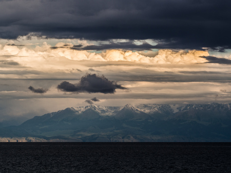 Amazing landscape with gold and dark clouds, snow peaks and water