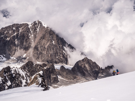 Beautiful mountain landscape with two climbers and cloudy background