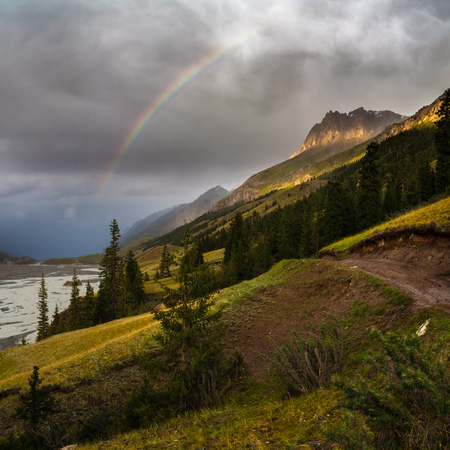 Wonderful mountain landscape with rainbow and sunny hills