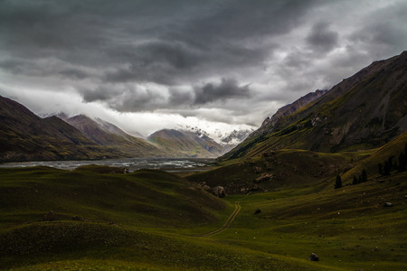 Cloudy landscape with thunderstorm in mountains with grass and road