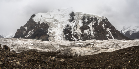 Cloudy mountain landscape with glacier. stones and snow peak