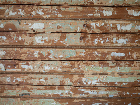 Old wood wall in log house with pieces of wallpapers and newspapers