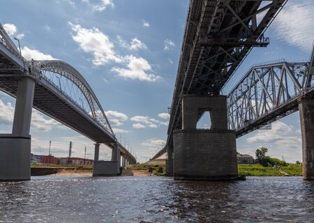 Three Railroad and road bridges over the Vilga river near the Nizhny Novgorod, Russia from bottom with blue sky background