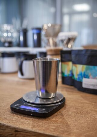 Metal glass on digital scales for coffee prepearing 스톡 콘텐츠