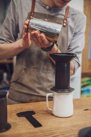 Barista puts coffee in aeropress. Alternative making coffee 스톡 콘텐츠
