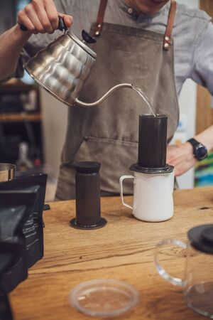 Barista pours water into an aeropress from a metal kettle