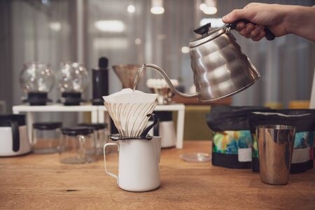 Barista wets paper coffee filter in funnel. Barista's hand hold metal kettle with boiling water