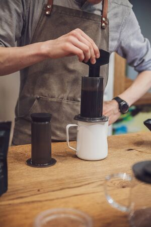 Barista making coffee with aeropress. Mixing coffee 스톡 콘텐츠