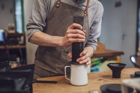 Barista making coffee. Barista's hands hold aeropress