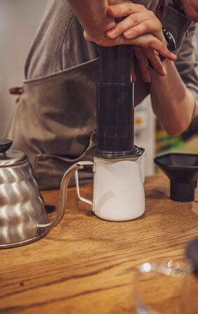 Barista pushing coffee in an aeropress. Alternative method.