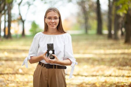 Attractive beautiful young girl holding retro vintage twin lens reflection camera in autumn park. Yellow leaves on the floor and background
