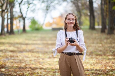 Attractive beautiful young girl holding modern mirror-less camera in autumn park.