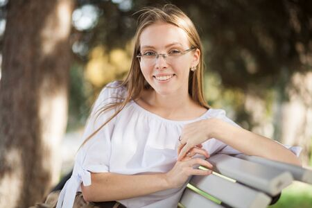 Beautiful attractive young girl in glasses sitting on the bench