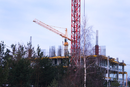Crane and building construction site at sunset, sunrise