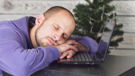 Tired Young Businessman in Office on New Year Eve. Christmas Tree in Office. Laptop on Desk. Business Concept. Man in Black Suit. Celebrating of New Year. Using Digital Device. Young Man. Banco de Imagens