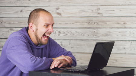 Smiling man sitting in office and working on laptop Banco de Imagens