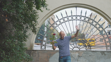man is waiting for his girl to meet with a rose and waving hisr hand. happy meeting