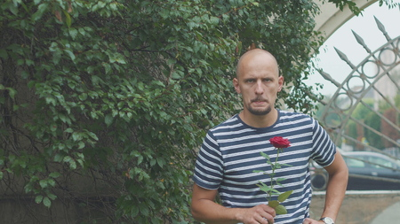sad young man with a rose waiting for a late woman Banco de Imagens