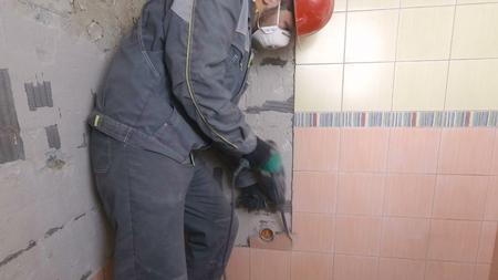 Demolition of old tiles with jackhammer. Renovation of old walls in the bathroom or kitchen Banco de Imagens