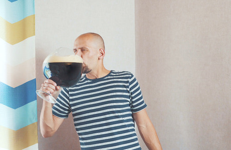 Happy, young man with a very large mug of beer. He laughs and rejoices, and then drinks.