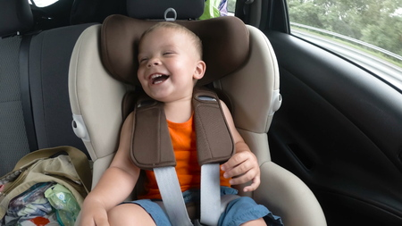 baby boy in the childrens car seat in the car. Kid smiles, laughs and waves his hands happily. Banco de Imagens