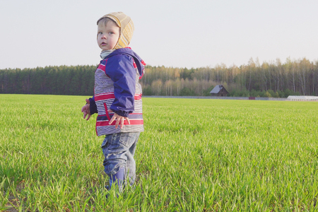 one year old boy farmer standing in the field with young wheat