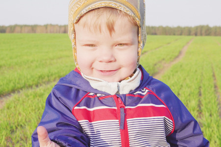 one year old boy farmer going in the field with young wheat. Closeup
