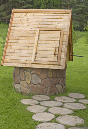 brink: Stone well with wooden roof on the brink of the forest