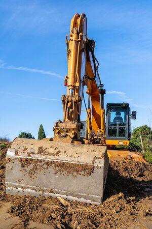 Excavadora amarilla de equipo pesado de la industria en el sitio de construcción