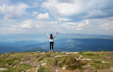 The girl is standing on the edge of the mountain with hands up Stock Photo