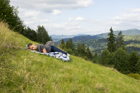 The girl is sleeping on a plaid on a mountainside Stock Photo